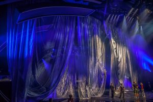 The concept involved five uniquely shaped and swaged drapes that appeared in seconds to conceal the stage space and to create 'props' for the artists to dance in and around.